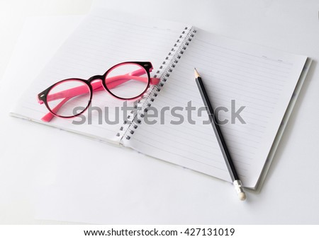 Glasses and pencil on notebook - stock photo