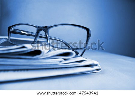 Glasses and stack of newspapers blue toned lying on the table - stock photo
