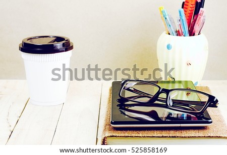 Glasses and tablet PC on brown notebook with a cup of coffee and office supply on wooden table in light gray background.