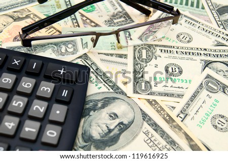 Glasses and the calculator on banknotes (dollars). - stock photo