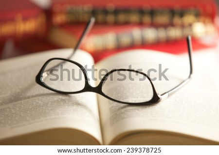Glasses are laying on a book . Short focus picture. Focus on glasses.Books in th e Background are unsharp.  - stock photo