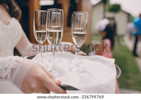 glasses at a wedding in the hands of the waiter with champagne - stock photo