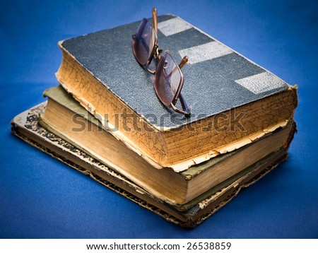 glasses at the top of the old books pile - stock photo
