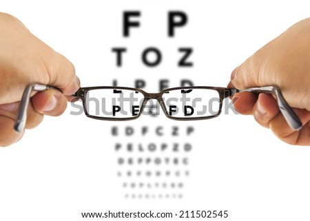 glasses being hold in front of an alphabet eyesight test charts isolated on white background - stock photo