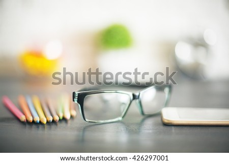 Glasses, blurry pencils, smart phone and other items in the background on dark wooden desktop