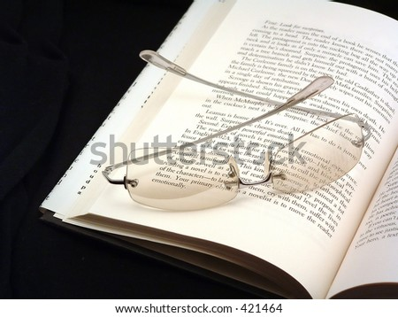 glasses, book and black background - stock photo