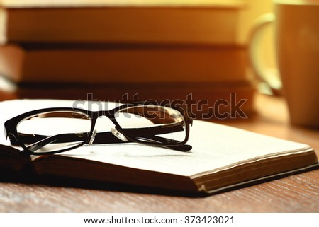 Glasses, book and cup of tea on a wooden table - stock photo