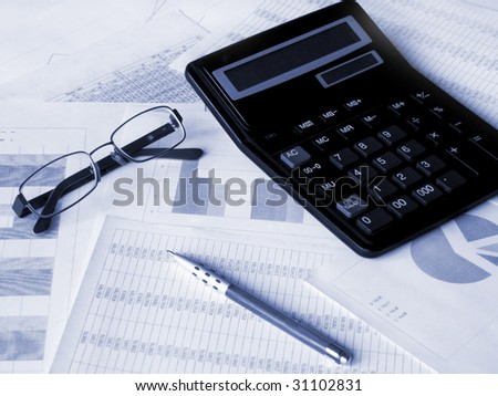 Glasses, calculator and pen on financial documents. Toned blue. Shallow DOF.