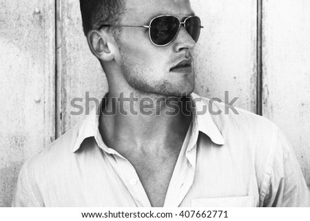 Glasses fashion beauty concept. Portrait of a young and handsome man in a white shirt and trendy glasses posing over wooden background. Close up. Street shot. - stock photo