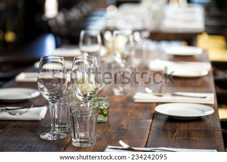 Glasses, flower fork, knife served  for dinner in restaurant with cozy interior - stock photo