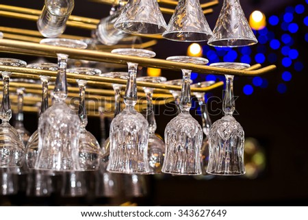 Glasses for alcoholic drinks hang above the bar