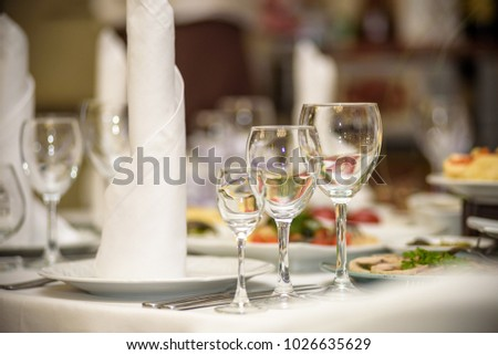 Glasses, forks, knives, napkins and decorative flower on a table served for dinner in cozy restaurant