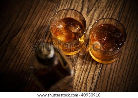 glasses from whisky and a bottle on a wooden table - stock photo