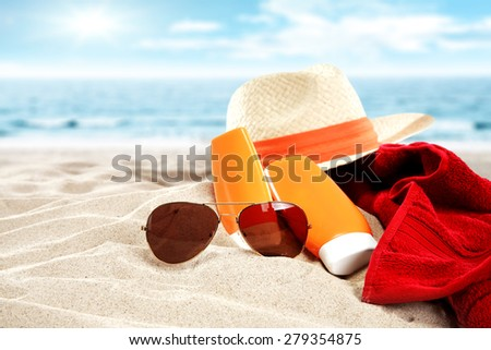 glasses hat suntan and red towel on beach  - stock photo