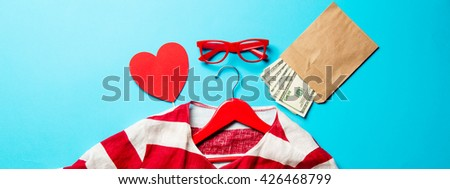 glasses, heart shaped toy, money, jacket on the hanger and laptop on the blue background - stock photo