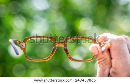 Glasses in hand. Blurred green spring background - stock photo