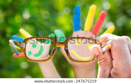 Glasses in hand. Smiley on hands against green spring blur background - stock photo