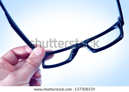 Glasses in the hand of a man in blue tones. - stock photo