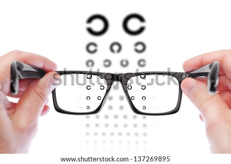 Glasses in the hands of men. Checking vision the table Golovin. - stock photo