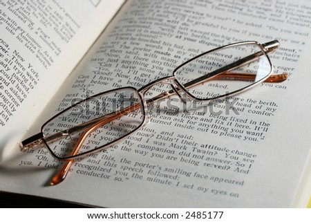 Glasses laying on page of the open book