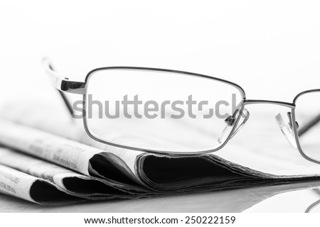 Glasses lies on the newspapers - stock photo