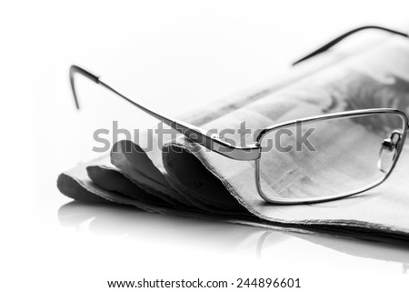 Glasses lies on the pile of newspapers - stock photo
