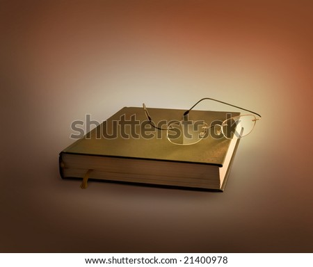 Glasses lying on the old  book - stock photo