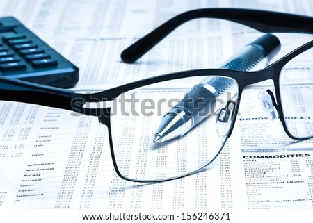 glasses near calculator with pen on financial newspaper under light tint blue  - stock photo