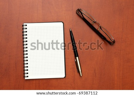glasses, notepad with pen lying on the table - stock photo