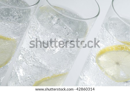 Glasses objects with soda water , ice cubes and lemon