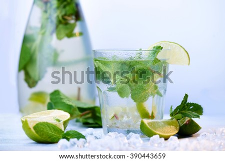 Glasses of a cold fresh lemonade drink with slices of lime on the glass, and decanter Slices of lime, ice and mint leaves on a  white wooden background. Copy space.  - stock photo