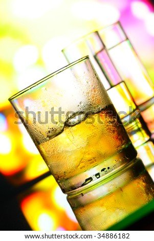 Glasses of alcohol closeup over colorful background - stock photo