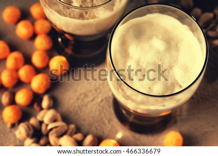 Glasses of beer, cheesballs and pistachio nuts