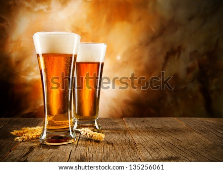 Glasses of beer on wooden table - stock photo