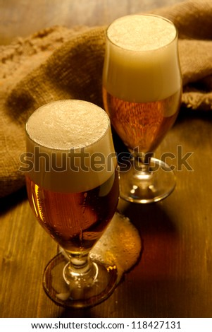 Glasses of beer on wooden table close-up - stock photo