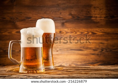 Glasses of beer with wheat ears on wooden planks - stock photo