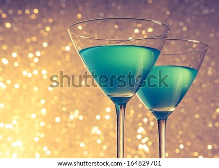 glasses of blue cocktail on golden and violet tint light bokeh background on table - stock photo