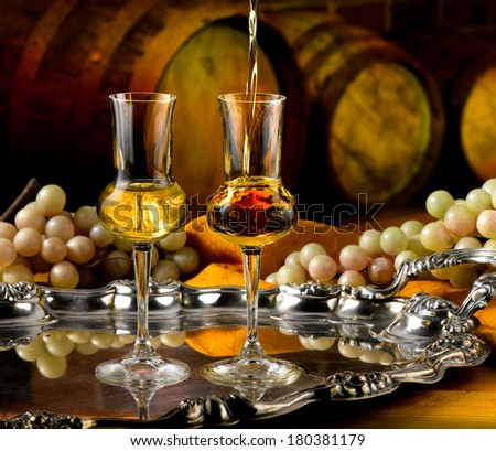 Glasses of brandy set in a cellar with barrels of reserves - stock photo