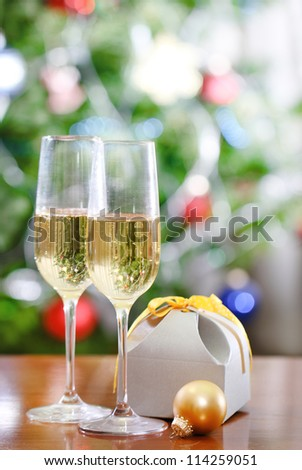 Glasses of champagne and Christmas present in front of Christmas tree for the holidays