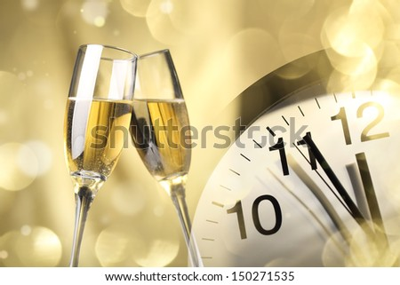 Glasses of champagne and clock close to midnight - stock photo