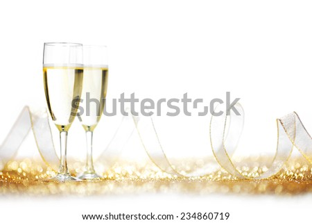 Glasses of champagne and ribbon on golden glitters isolated on white - stock photo