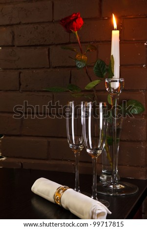 glasses of champagne and rose with candle against brick wall