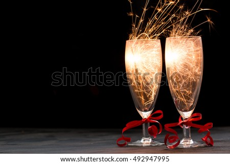 Glasses of champagne and sparklers on black background , merry christmas concept