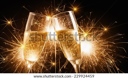 Glasses of champagne and sparklers on bright background with sparklers - stock photo
