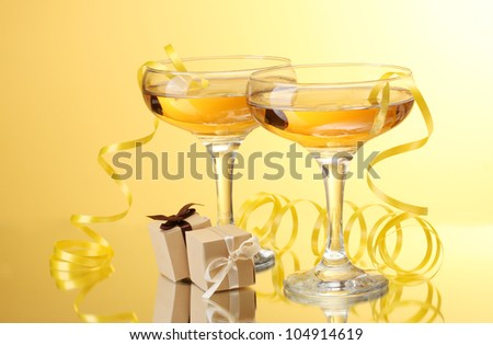 glasses of champagne, gifts and streamer on yellow background - stock photo