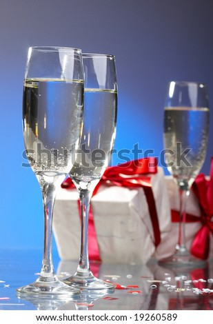 Glasses of champagne, gifts with red tapes and bows