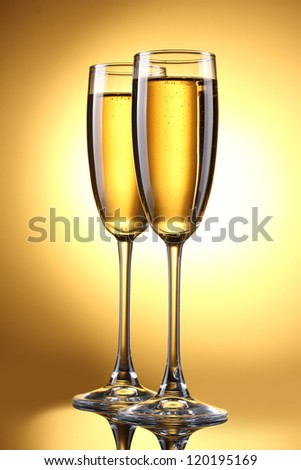glasses of champagne on yellow background