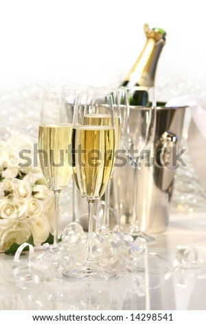 Glasses of champagne, roses, and a bottle of champagne - stock photo