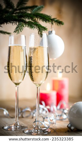Glasses of champagne under decorated christmas tree branch - stock photo