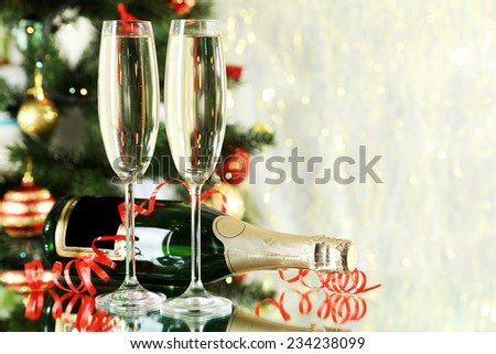Glasses of champagne with bottle on a lights background - stock photo